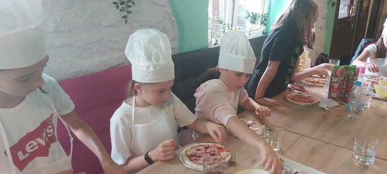 uczniowie klasy czwrtej dzielący w pizzeri pizzę na kawałki, nauka ułamków