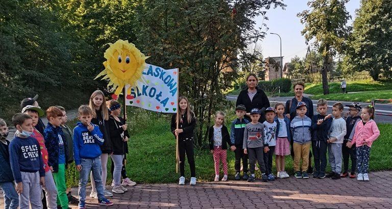 przedszkolaki i uczniowie z klucz z plakatem odblaskowa szkoła