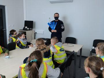uczniowie klasy 3 słuchający na posterunku policji pogadanki na temat bezpieczeństwa