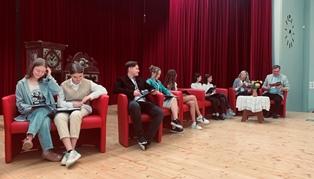 Uczniowie i goście siedzący i czytający w auli szkolnej