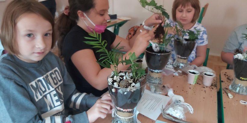 trzy uczennice klasy czwartej siedzące w klasie przy wspólnym stole, tworzące kompozycje kwiatowe w szklanych doniczkach