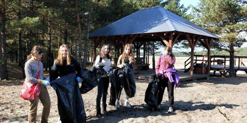 uczennica na pustyni z workami na śmieci, sprzątają naszą gminę